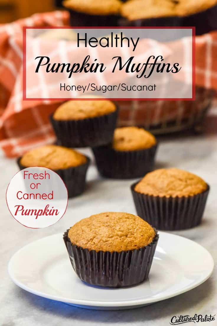 Healthy Pumpkin Muffin shown on a white plate in front of a stack of muffins and basket of muffins