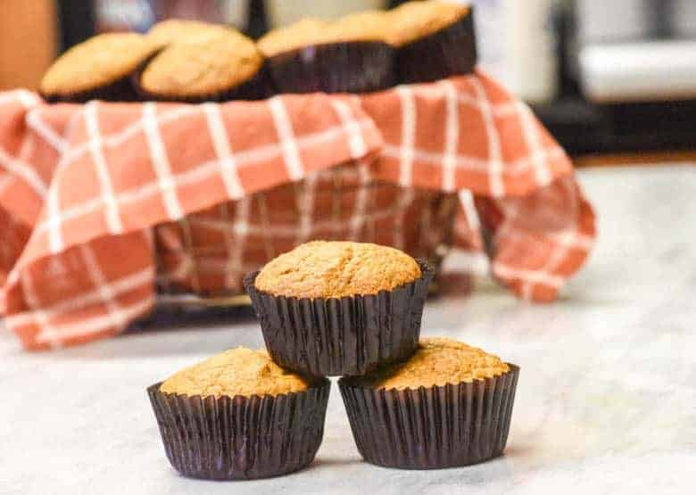 3 Healthy Pumpkin Muffins stacked in front of a basket of muffins with a coral and white checked napkin lining it.