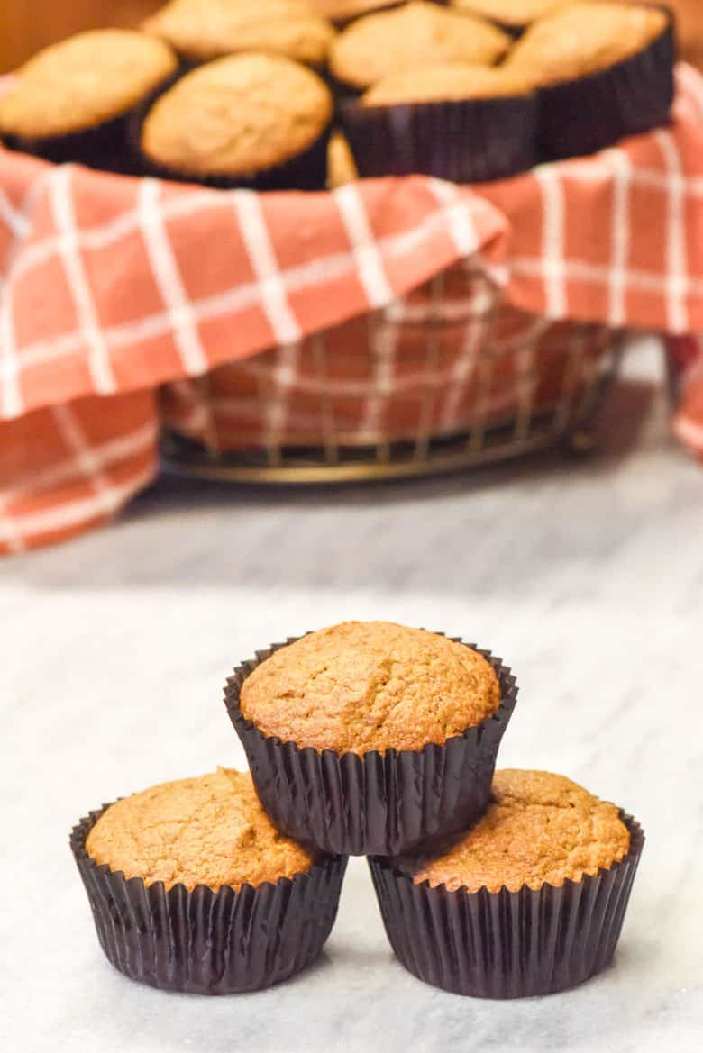 Healthy Pumpkin Muffins Recipe shown and 3 muffins stacked in a pyramid in front of a basket of muffins.