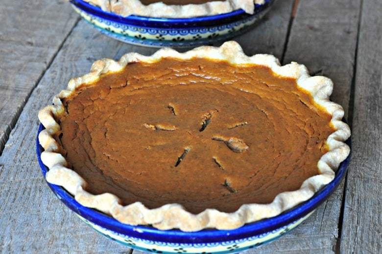 A homemade pie crust in a pie dish with filling