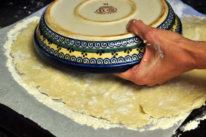 A photo showing the homemade pie crust dough getting transferred to a pie dish