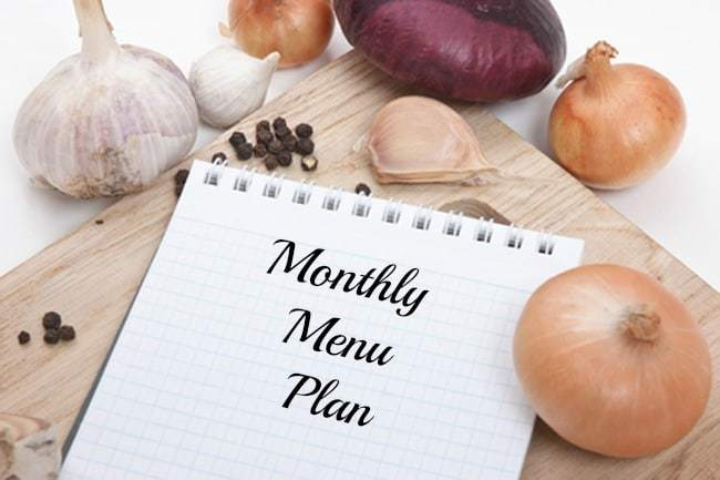 menu planning - notebook for menu planning on a cutting board