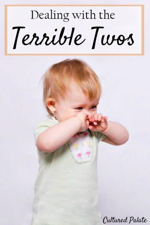 Child standing with hands over face as if pouting