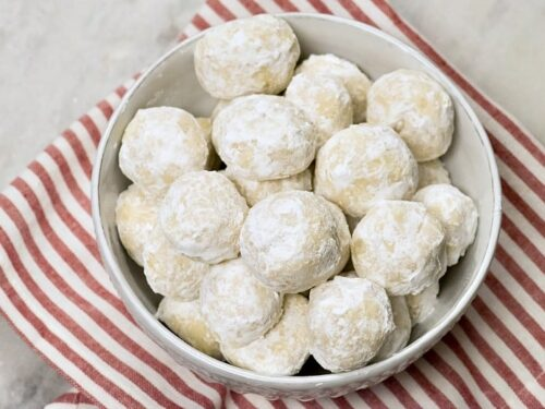 A white bowl of Italian Wedding cookies also known as Mexican Wedding Cookies on a red and white striped napkin.