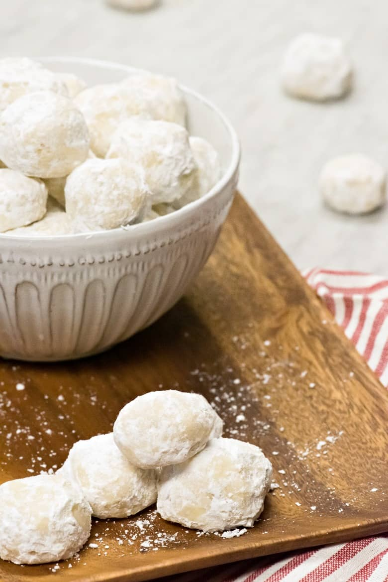 White bowl of Wedding Cookies on a wooden tray with a striped napkin on marble counter.