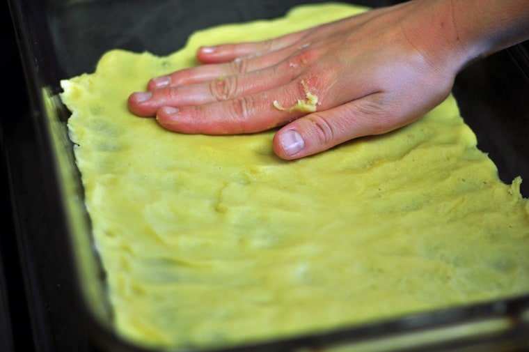 A hand patting pastry ingredients to make angle wings cookies into a tray