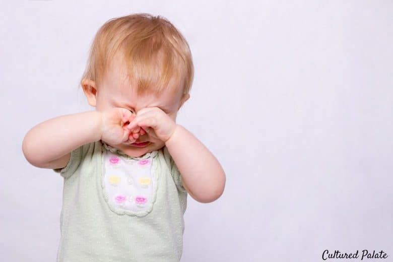 photo of a two year old standing rubbing eyes as if crying from the post, Are the Terrible Twos Really Terrible