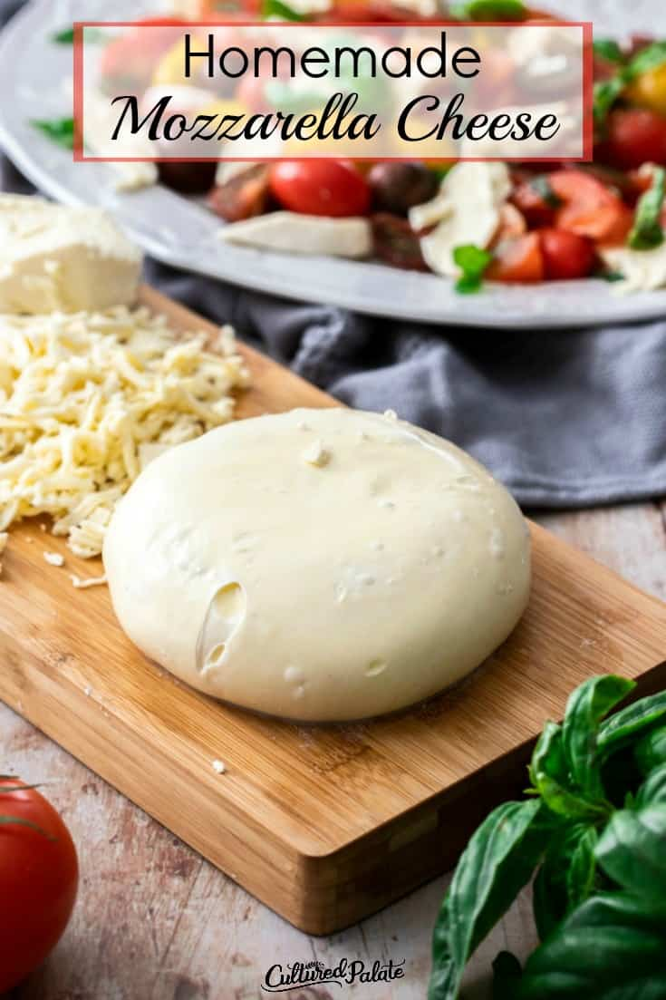 Homemade Mozzarella Cheese round shown on cutting board with grated cheese in background.
