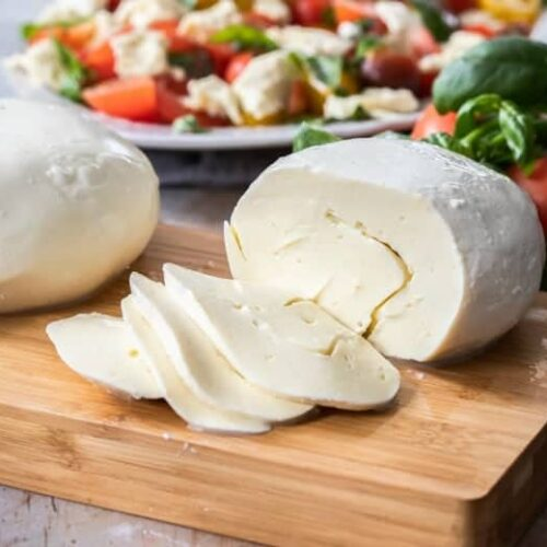 Homemade Mozzarella Cheese sliced on wooden cutting board with salad in background.