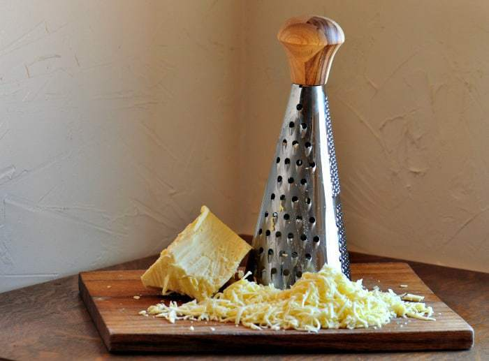 a grater sitting on a chopping board with grated mozzarella cheese