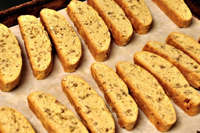 Pecan biscotti sitting on a lined baking tray ready for second baking