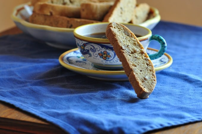 Pecan biscotti sitting on the edge of a cup of coffee on a blue tablecloth