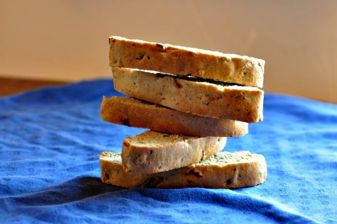 Pecan biscotti stacked on top of each other sitting on a blue tablecloth