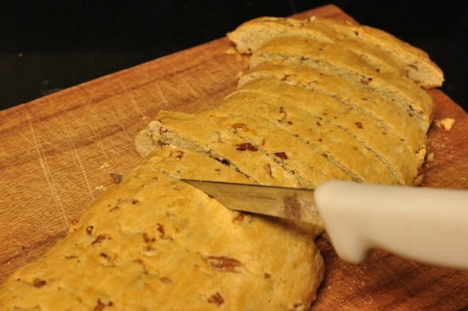 Pecan biscotti recipe dough baked on chopping board being cut into individual cookies