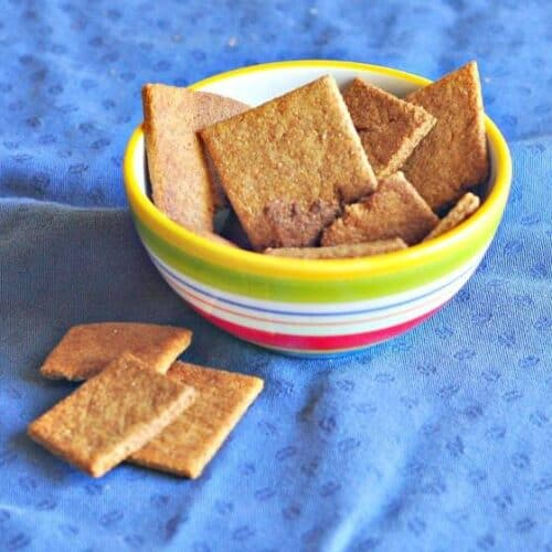 Homemade Wheat Thins Recipe shown in a bowl on blue tablecloth