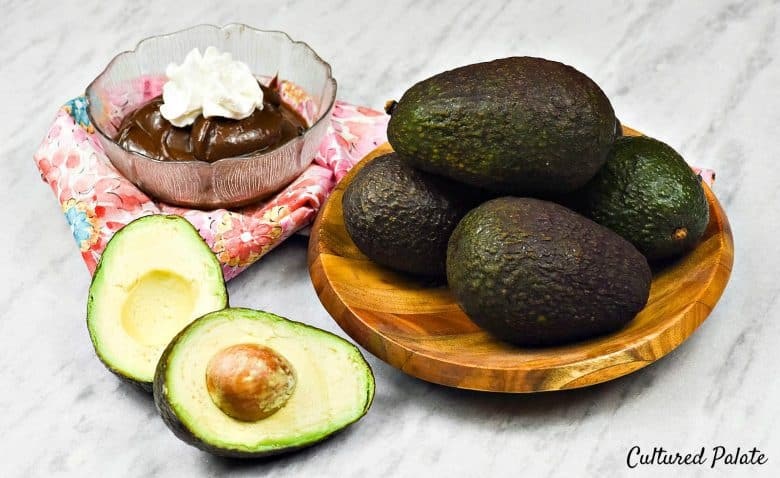 Chocolate Avocado Pudding  - a bowl of pudding with ripe avocados in a bowl and one cut open