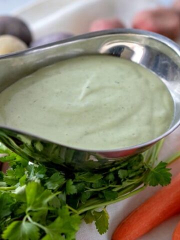Green Goddess Dressing Recipe shown in silver pouring dish with veggies around it.