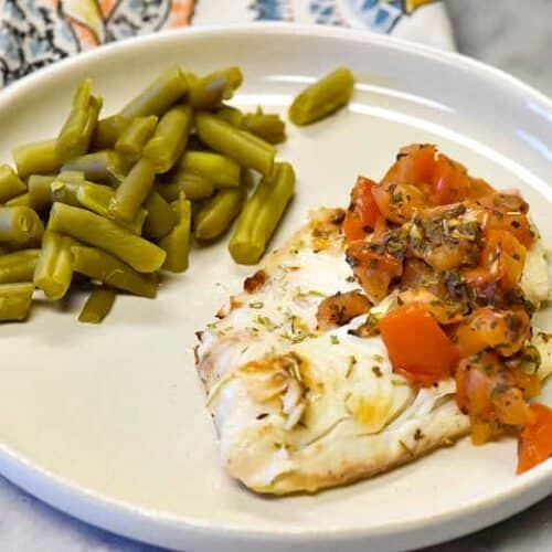 Tomato Basil Grilled Fish recipe shown close up with napkin and green beans.