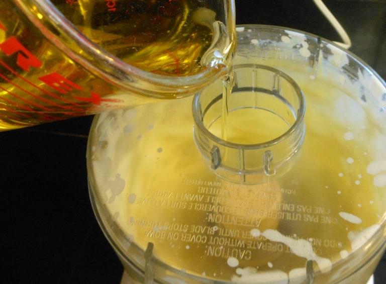 A process shot of pouring olive oil into a food processor to make lacto fermented mayonnaise