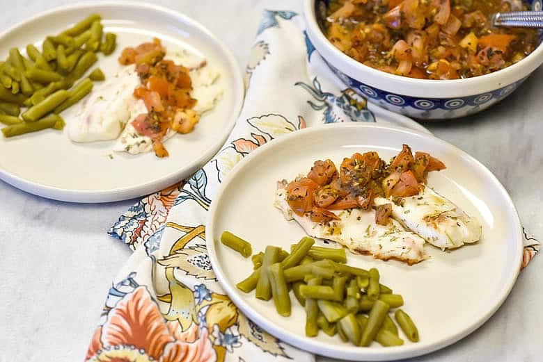 Tomato Basil Grilled Fish Recipe shown on plates with tomatoes in bowl on marble counter.