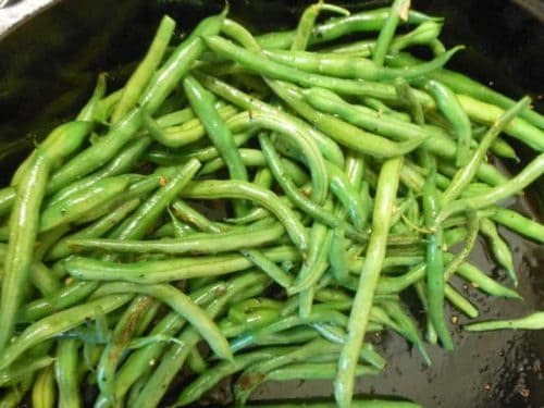 A close up shot of garlicky green beans in a pan