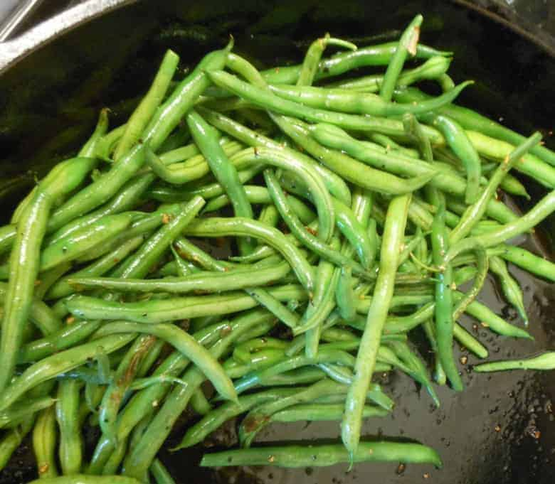 A close up of garlic green beans in a cast iron skillet
