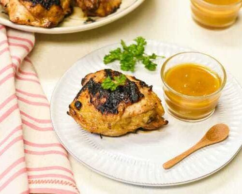 honey mustard grilled chicken shown on a white plate with dipping sauce to the side and plate in the background