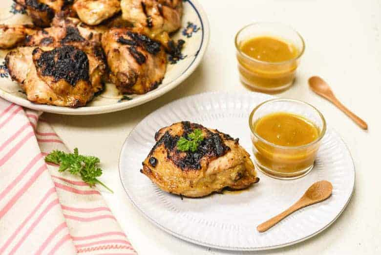 grilled chicken from the Honey Mustard Chicken recipe shown on a white plate with dipping sauce to the side and more chicken in the background