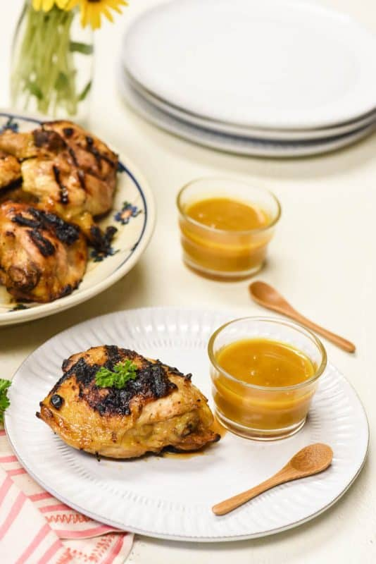 vertical image of grilled chicken from the Honey Mustard Chicken recipe shown on a white plate with dipping sauce to the side and more chicken in the background