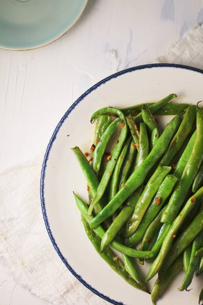 Sautéed Green Beans With Garlic shown from overhead on a blue trimmed white plate.