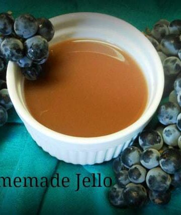 A photo of homemade jello in a white bowl with grapes at the side