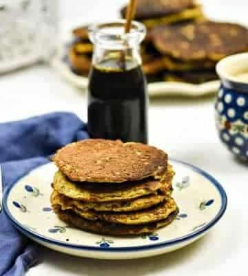 Butternut Squash Pancakes on a plate with syrup in the background