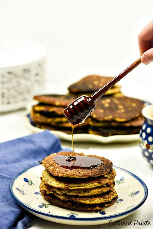 Butternut Squash Pancakes - Paleo Pancakes shown on plate with honey being drizzled over them.