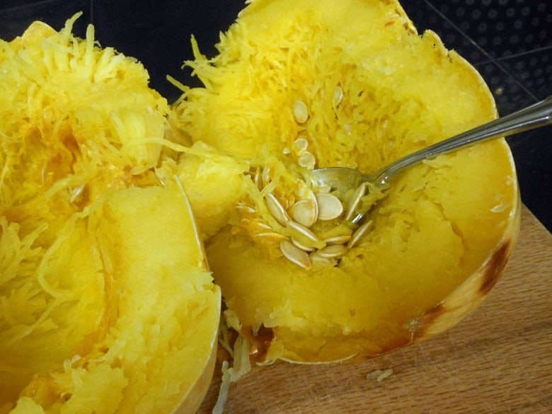 A close up of spaghetti squash noodles and removing the seeds