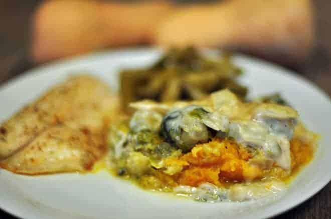 A close up shot of a Brussels sprouts casserole with squash on a white plate