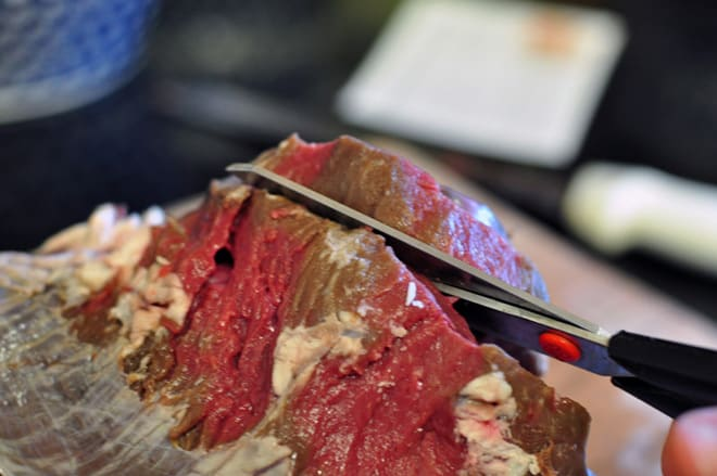 A pair of scissors cutting beef heart to make beef heart kabobs