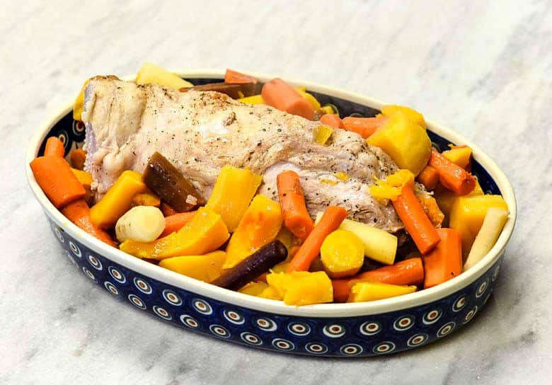 Oven Roasted Pork Loin with veggies in a polish pottery dish.