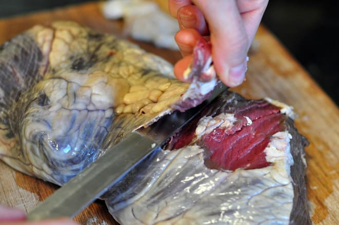 A photo of two hands cutting a beef heart to make beef heart kabobs
