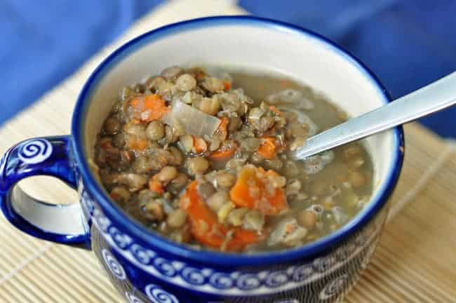 Lentil Soup Middle Eastern Style in a large blue mug on a wooden surface