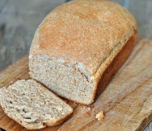 whole wheat bread with a slice cut on a wooden board
