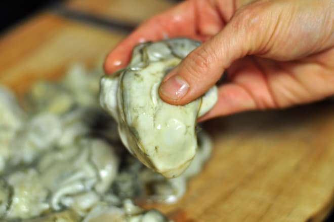 A close up shot of a hand holding an oyster for oyster stew