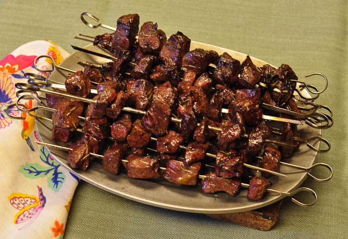 A pile of beef heart kabobs on a serving plate