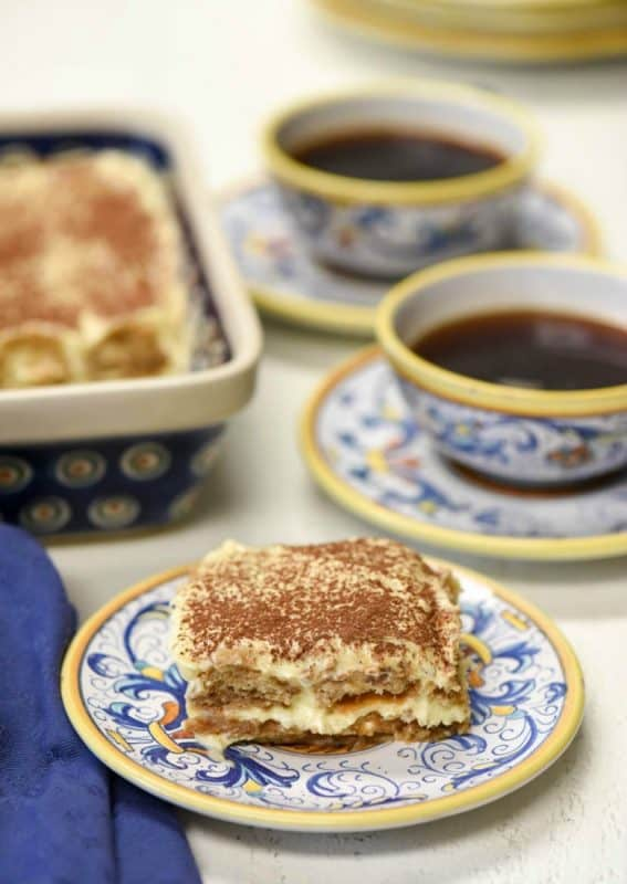 a piece of easy tiramisu recipe shown on plate with cups of coffee
