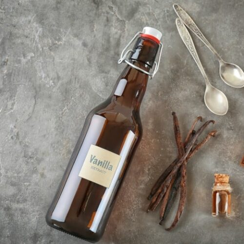 Brown bottle of homemade vanilla extract shown with vanilla beans and spoons from the post How to Make Vanilla Extract