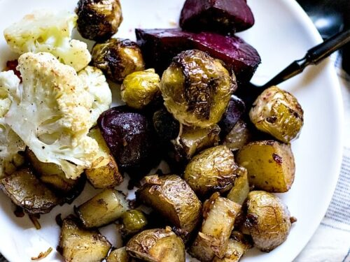 Roasted vegetables shown on white plate with black fork.