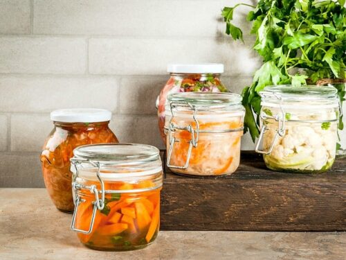 Fermented foods shown in different canning jars with subway tile in the background.