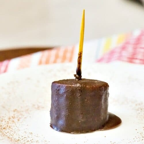A single Chocolate Covered Banana Bite on a white plate with yellow toothpick and colorful napkin.