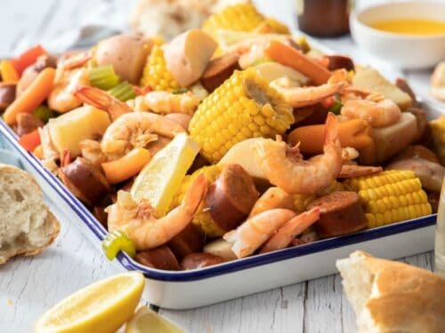 Shrimp boil recipe shown ready to eat in enamel container on wooden table.