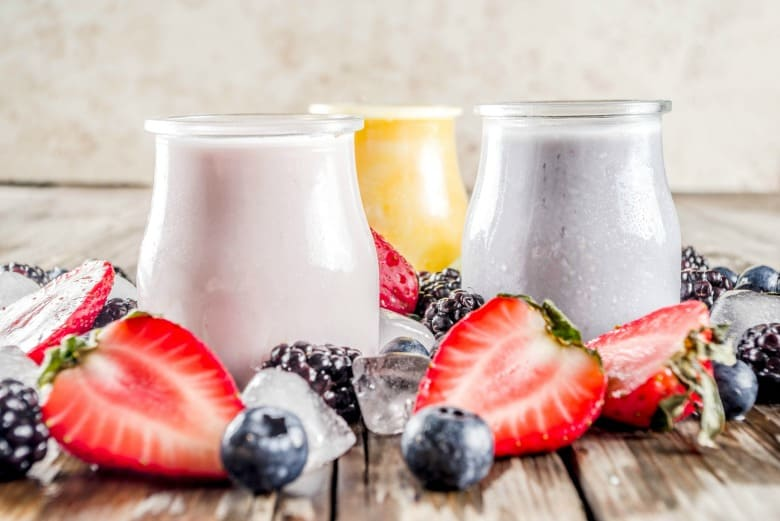 Kefir Smoothie shown in three flavors with ice, strawberries and blueberries around glass jars.