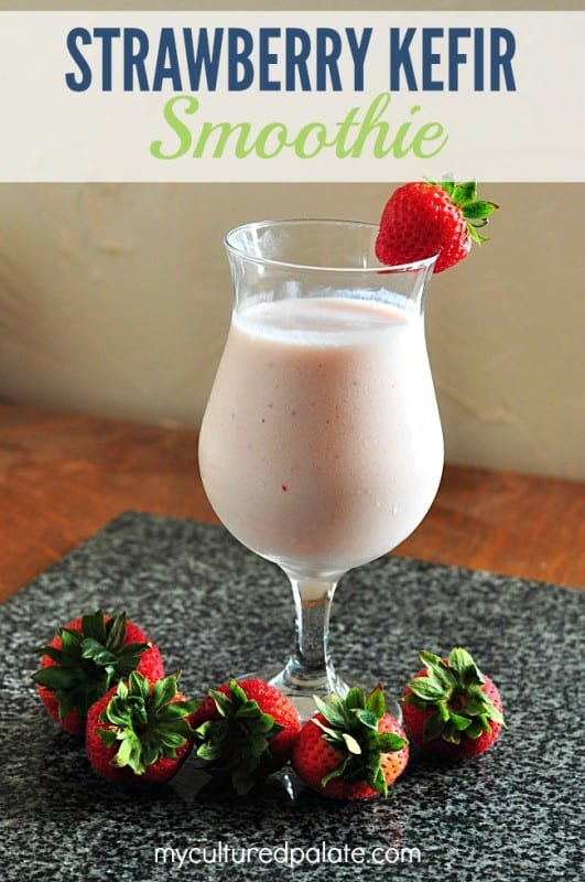 A photo of a Strawberry Kefir Smoothie with a strawberry on the side of the glass